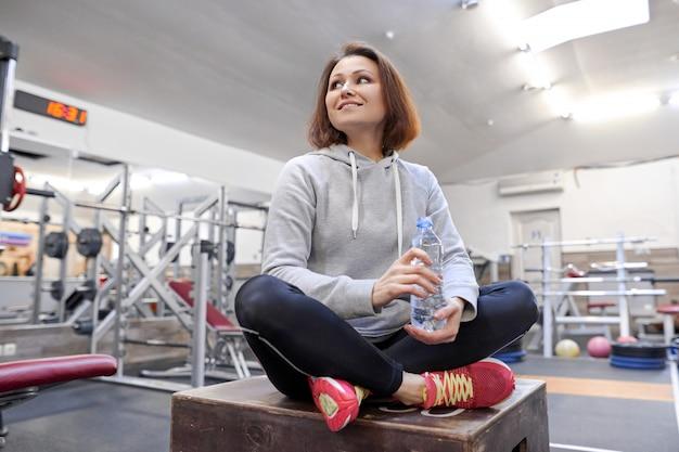 Portret uśmiechnięta lato kobieta z butelką woda w gym