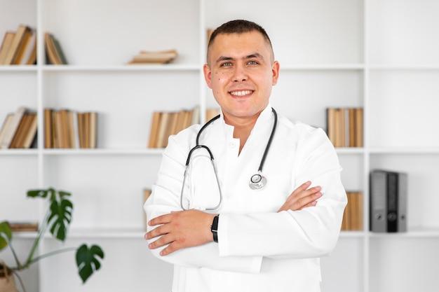 Portret uśmiechnięta lekarka z przecinającymi rękami