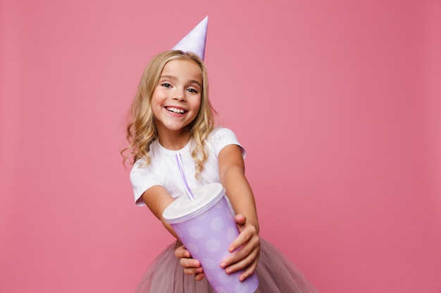 Portret uśmiechnięta mała dziewczynka w urodzinowym kapeluszu