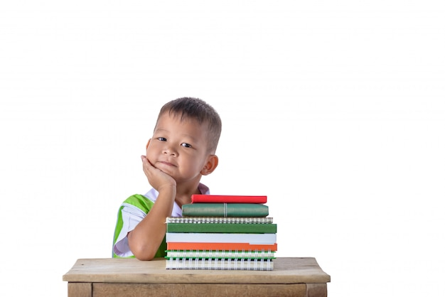 Portret uśmiechnięta mała studencka azjatykcia chłopiec z wiele książkami