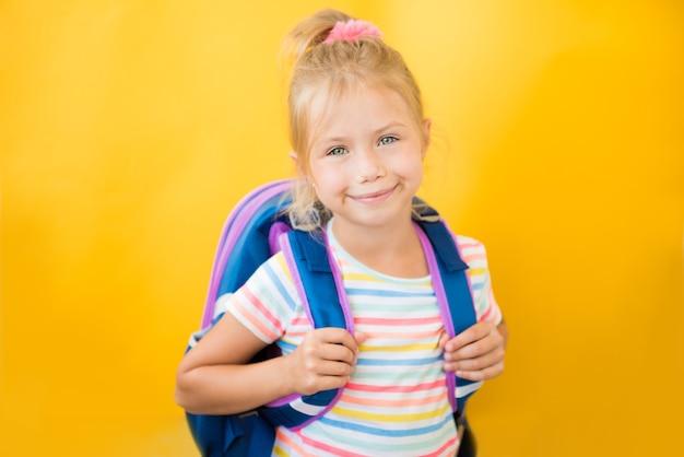 Portret uśmiechnięta mała uczennica z plecakiem na żółtej ścianie