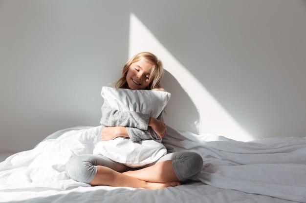 Portret uśmiechnięta małej dziewczynki przytulenia poduszka