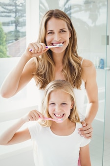 Portret uśmiechnięta matka i córka szczotkuje zęby