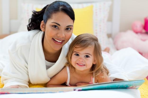 Portret uśmiechnięta matka i jej córka czyta wpólnie