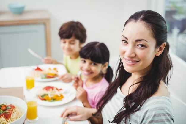 Portret uśmiechnięta matka z dziećmi przy łomotać stół