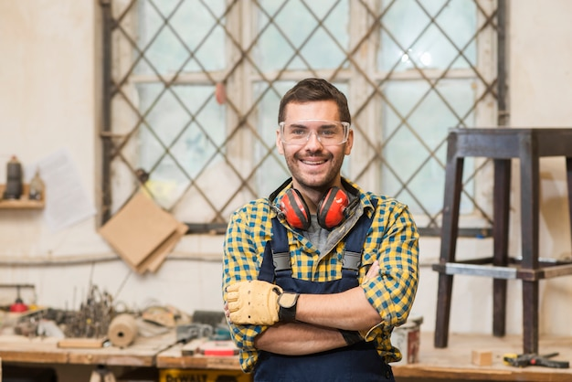 Portret uśmiechnięta męska cieśla pozycja przed workbench