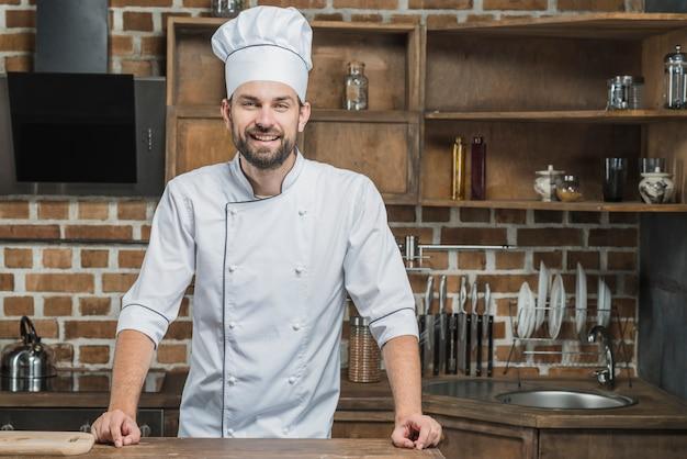 Portret uśmiechnięta męska szef kuchni pozycja w kuchni