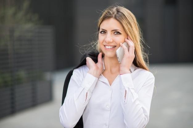 Portret uśmiechnięta młoda biznesowa kobieta opowiada na telefonie