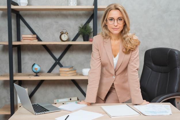 Portret uśmiechnięta młoda bizneswoman pozycja przy miejscem pracy w biurze