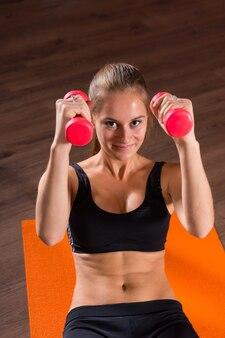 Portret uśmiechnięta młoda blond kobieta robi brzuszki brzucha z ciężarkami na jasnopomarańczowej macie podłogowej i patrząc na kamerę w studio ćwiczeń