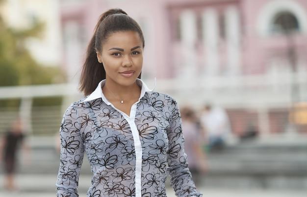 Portret uśmiechnięta młoda czarna kobieta stojąca na zewnątrz.