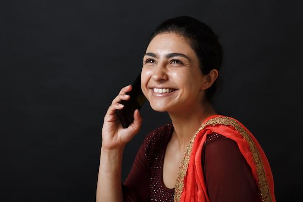 Portret uśmiechnięta młoda dorosła kobieta indyjska w sari rozmawia telefon komórkowy na czarnym tle.