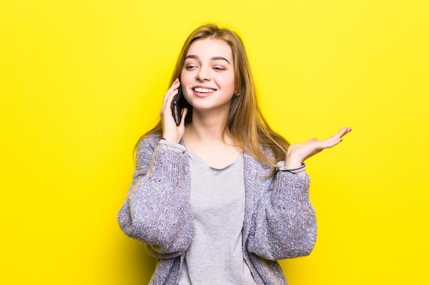 Portret uśmiechnięta młoda dziewczyna nastolatka z nawiasami klamrowymi rozmawia przez telefon komórkowy na białym tle