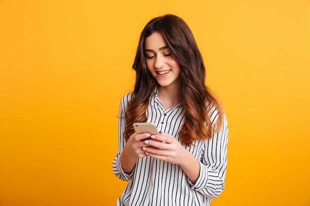 Portret uśmiechnięta młoda dziewczyna używa telefon komórkowego