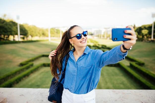 Portret uśmiechnięta młoda dziewczyna w okularach przeciwsłonecznych co selfie zdjęcie w parku