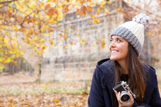 Portret uśmiechnięta młoda dziewczyna w zimowe ubrania w jesiennym krajobrazie. w ręku trzyma starodawny aparat. miejsce na tekst.