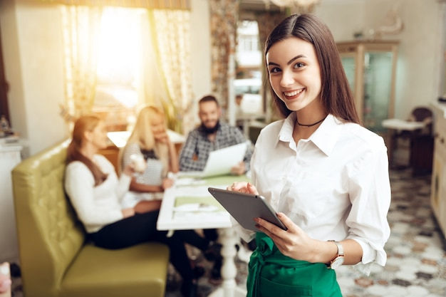 Portret uśmiechnięta młoda kelnerka stoi w kawiarni