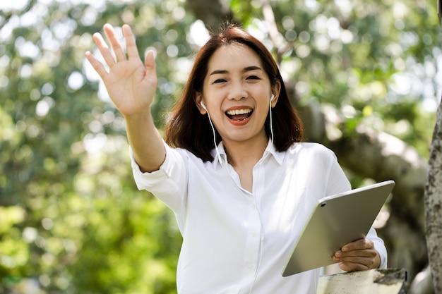 Portret uśmiechnięta młoda kobieta biznesu za pomocą tabletu do połączenia wideo z przyjacielem w parku