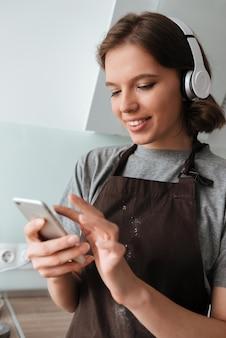 Portret uśmiechnięta młoda kobieta jest ubranym fartucha w hełmofonach