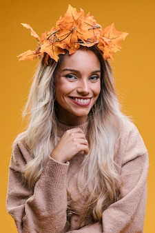 Portret uśmiechnięta młoda kobieta ma na sobie liście klonu tiara przeciwko żółtej ścianie