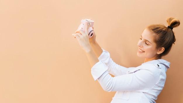 Portret uśmiechnięta młoda kobieta opowiada jaźń portret z różową natychmiastową kamerą przeciw brown tłu