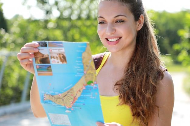 Portret uśmiechnięta młoda kobieta patrząc na mapę w parku w lecie