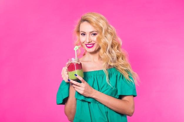 Portret uśmiechnięta młoda kobieta pije sok smoothie na różowym tle.