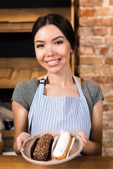 Portret uśmiechnięta młoda kobieta pokazuje eclairs przy piekarnia kontuarem
