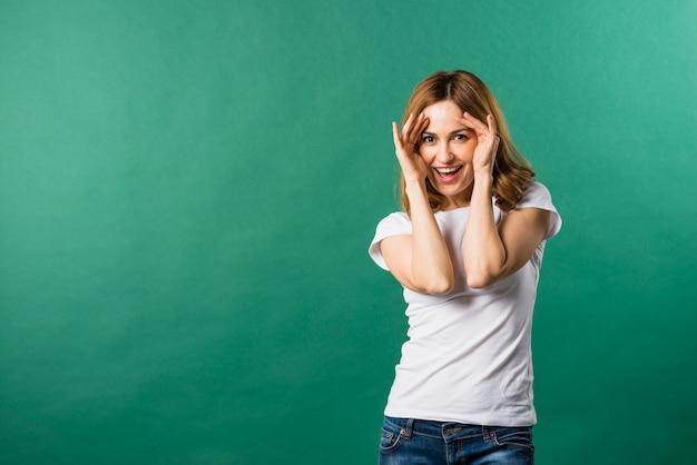 Portret uśmiechnięta młoda kobieta przeciw zielonemu tłu