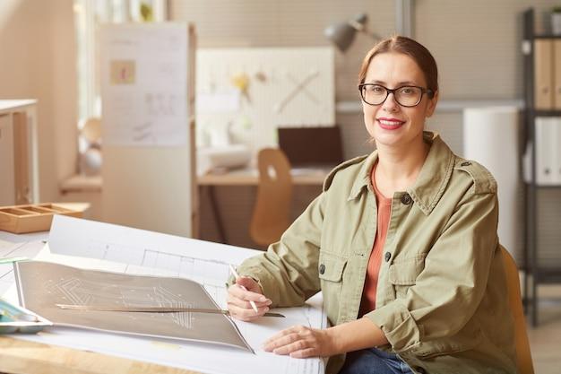 Portret uśmiechnięta młoda kobieta rysująca plany i plany podczas pracy przy biurku w biurze inżynierów,
