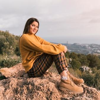 Portret uśmiechnięta młoda kobieta siedzi na szczycie góry patrząc na kamery