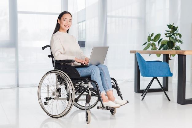 Portret uśmiechnięta młoda kobieta siedzi na wózku inwalidzkim, patrząc na kamery z laptopem na kolanach