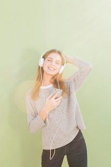 Portret uśmiechnięta młoda kobieta słucha muzykę na hełmofonie przeciw mennicy zieleni tłu