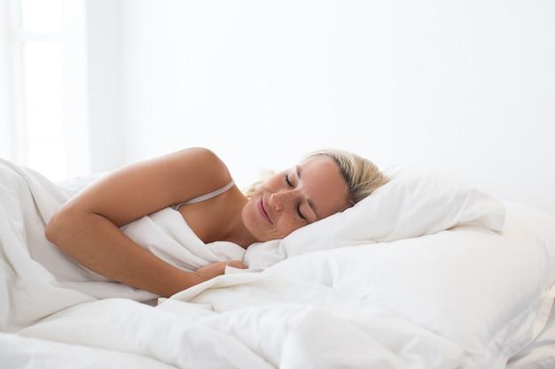 Portret uśmiechnięta młoda kobieta śpi w łóżku