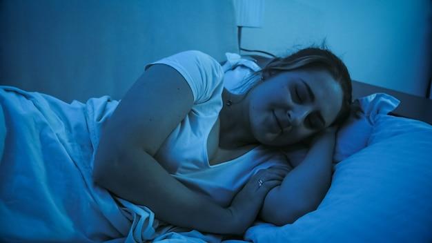 Portret uśmiechnięta młoda kobieta śpi w nocy i ma dobre sny.