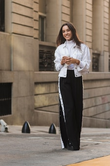 Portret uśmiechnięta młoda kobieta trzyma jednorazową filiżankę w ręce