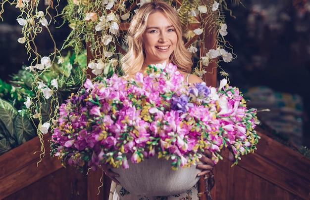 Portret uśmiechnięta młoda kobieta trzyma kolorową kwiat wazę w ręce