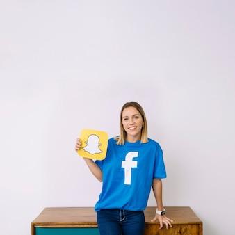 Portret uśmiechnięta młoda kobieta trzyma snapchat logo