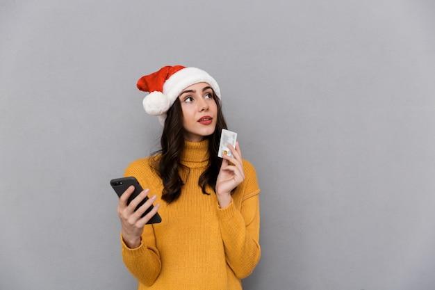 Portret uśmiechnięta młoda kobieta ubrana w czerwony kapelusz świętego mikołaja stojącego na białym tle na szarym tle, przy użyciu telefonu komórkowego, pokazując plastikową kartę kredytową