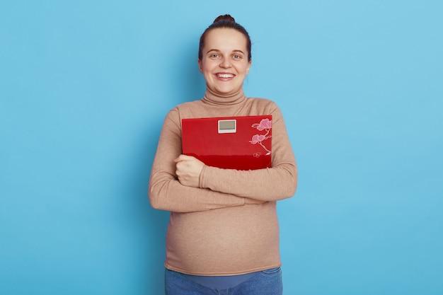 Portret uśmiechnięta młoda kobieta w ciąży trzyma czerwoną skalę w rękach