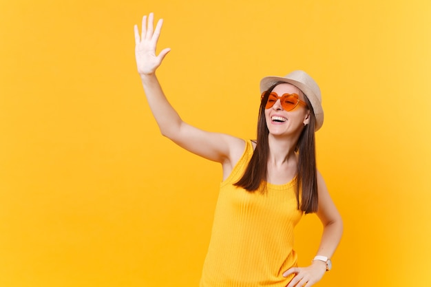 Portret uśmiechnięta młoda kobieta w słomkowym letnim kapeluszu, pomarańczowe okulary machając ręką i pozdrawiając, jak zauważa kogoś, skopiuj miejsce na białym tle na żółtym tle. koncepcja życia ludzi. powierzchnia reklamowa.