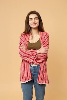 Portret uśmiechnięta młoda kobieta w strojach casual patrząc na kamery, trzymając się za ręce skrzyżowane na białym tle na pastelowym beżowym tle w studio. ludzie szczere emocje, koncepcja stylu życia. makieta miejsca na kopię.