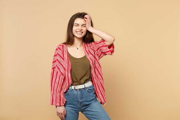 Portret uśmiechnięta młoda kobieta w ubraniach casual, trzymając zamknięte oczy, kładąc rękę na głowie na białym tle na pastelowym beżowym tle w studio. koncepcja życia szczere emocje ludzi. makieta miejsca na kopię.