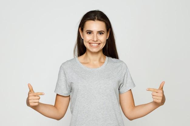 Portret uśmiechnięta młoda kobieta wskazuje palcem na miejsce na kopię na koszulce