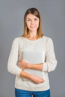 Portret uśmiechnięta młoda kobieta z laptopem na popielatym tle