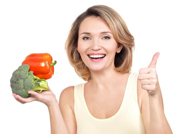 Portret uśmiechnięta młoda kobieta z warzywami na białym tle.