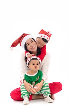 Portret uśmiechnięta młoda matka z dwoma synami świętować na białym tle