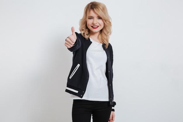 Portret uśmiechnięta młoda młoda kobieta stoi aprobaty i pokazuje w przypadkowych ubraniach