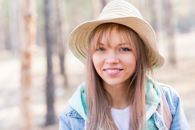 Portret uśmiechnięta młoda żeńska turystyczna jest ubranym kapelusz patrzeje kamerę