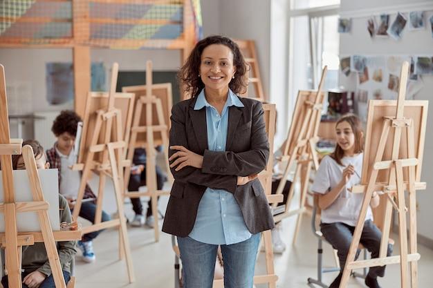Portret uśmiechnięta nauczycielka w nowoczesnej klasie z dziećmi lekcji rysunku w tle